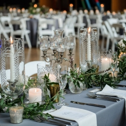 Sarah Grimshaw Designs created a stunning tablescape featuring greenery accents and vintage glass hurricanes