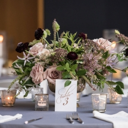 Greenery centerpieces featured lush purples and blush accents created by Sarah Grimshaw Designs