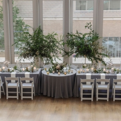 Stunning head table features cool gray linens and over sized greenery centerpieces for a summer wedding coordinated by Magnificent Moments Weddings at The Mint Museum Uptown