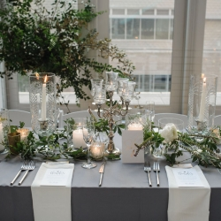 Stunning tablescapes by Sarah Grimshaw Design for a summer wedding at The Mint Museum Uptown featured vintage glass hurricanes and lush greenery