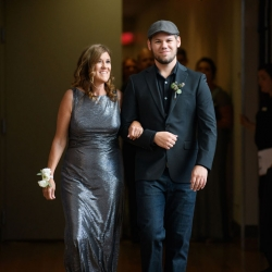 Groom escorts his mother down the aisle during his summer wedding at The Mint Museum Uptown