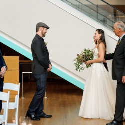 Brides escorts her to her groom during their summer wedding ceremony in Uptown Charlotte, North Carolina