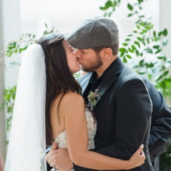 Julia Laible Photography captures a kiss between bride and groom during their wedding ceremony at The Mint Museum Uptown