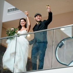 Bride and groom raise a toast to their guests during their wedding reception coordinated by Magnificent Moments Weddings at The Mint Museum Uptown