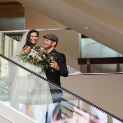Bride and groom smile as they enter their wedding reception at The Mint Museum Uptown during their summer wedding coordinated by Magnificent Moments Weddings