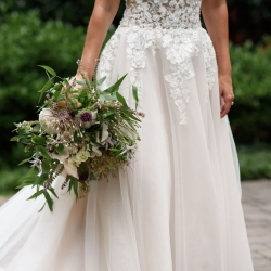 Birde shows off the lace details of her dress and the bridal bouquet she will hold during her summer wedding at The Mint coordinated by Magnificent Moments Weddings