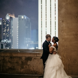 Bride and groom pose among Charlotte Skyscrapers during their summer wedding at The Mint Museum Uptown