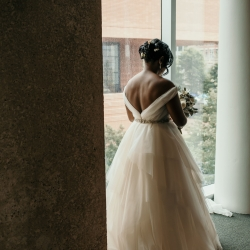 Bride poses at The Mint Museum Uptown during her summer wedding captured by Kelly Meyers Photography