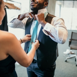 Bridesman puts on the final details of his suite for a summer wedding captured by Kelly Meyers Photography