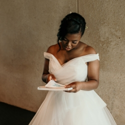 Bride reads a sweet card from her groom before walking down the aisle to her summer wedding ceremony at The Mint