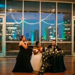 Bride and groom enjoy being toasts by family and friends during their uptown wedding coordinated by Magnificent Moments Weddings