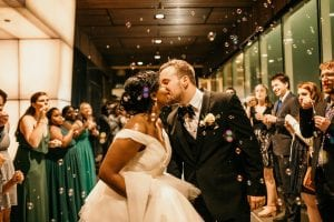 Bride and groom share one more kiss under a sea of bubbles captured by Kelly Meyers Photography