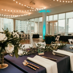Market lights and navy linens create a modern vibe for a wedding coordinated by Magnificent Moments Weddings