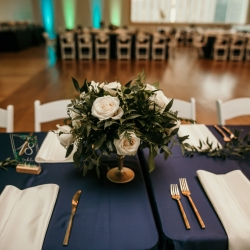 Deep navy linens are accented by greenery centerpieces created by April Floral Expressions for a summer wedding at The Mint