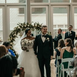 Bride and groom exit their ceremony at The Mint Museum Uptown after exchanging vows