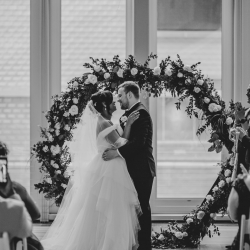 Bride and groom share a kiss in front of a stunning arch from Evermore Rentals during their Uptown Charlotte Wedding
