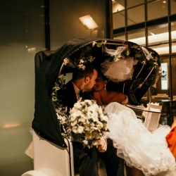 Bride and groom share one last kiss in their getaway cart after their stunning wedding at The Mint Museum Uptown