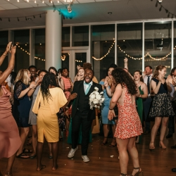 Bridesman is excited after catching the bouquet during a summer wedding reception coordinated by Magnificent Moments Weddings