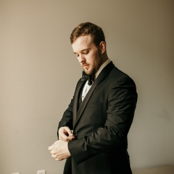 Groom puts the final touches on his look by adding cufflinks while Kelly Meyers captures the details for a summer wedding in Uptown Charlotte