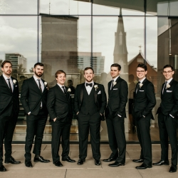Groom poses with his groomsmen during his summer wedding at The Mint Museum Uptown