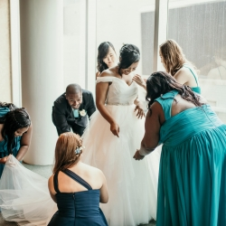 Brides bridal party helps get her ready to walk down the aisle to her ceremony coordinated by Magnificent Moments Weddings