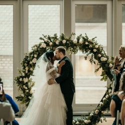 Bride and groom share a kiss after exchanging vows in front of a modern arch rented from Evermore and covered in flowers by April's Floral Expressions