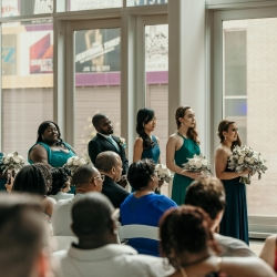 Bridal party observes the vows during a spring wedding coordinated by Magnificent Moments Weddings