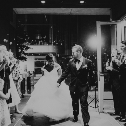 Bride and groom exit through a sea of bubbles in a grande event coordinated by Magnificent Moments Weddings