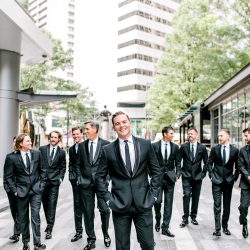 Groom poses with his groomsmen in Uptown Charlotte for Kieran Claire Photography