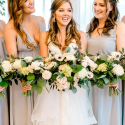 Bride and bridesmaids show of the stunning work of Jimmy Blooms in their bouquets