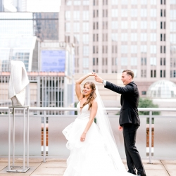 Groom gives his bride a spin in Uptown Charlotte during their spring wedding coordinated by Magnificent Moments Weddings