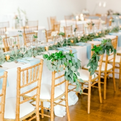 Greenery accents created by Jimmy Blooms show off the brides and grooms chairs during a spring wedding at Foundation for the Carolinas