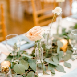 Soft pink roses in simple bud vases were delicate centerpieces for a spring wedding at Foundation for the Carolinas