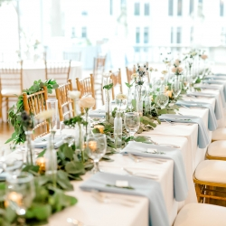 Gold chivari chairs, crisp white linens, soft blue napkins, and green accents created the perfect table setting for a spring wedding captured by Kieran Claire Photography