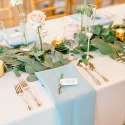 Simple white linens, soft pink napkins, and long stem roses were the perfect table setting for a spring wedding at Foundation for the Carolinas