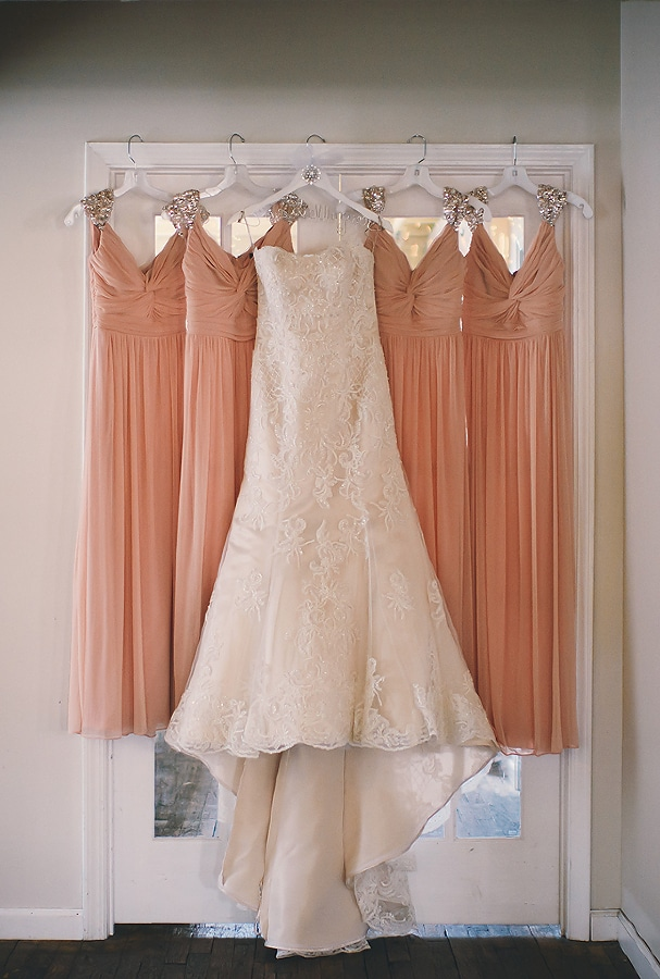 bridal gown from Poffie girls hanging up with bridesmaid dresses from David's Bridal