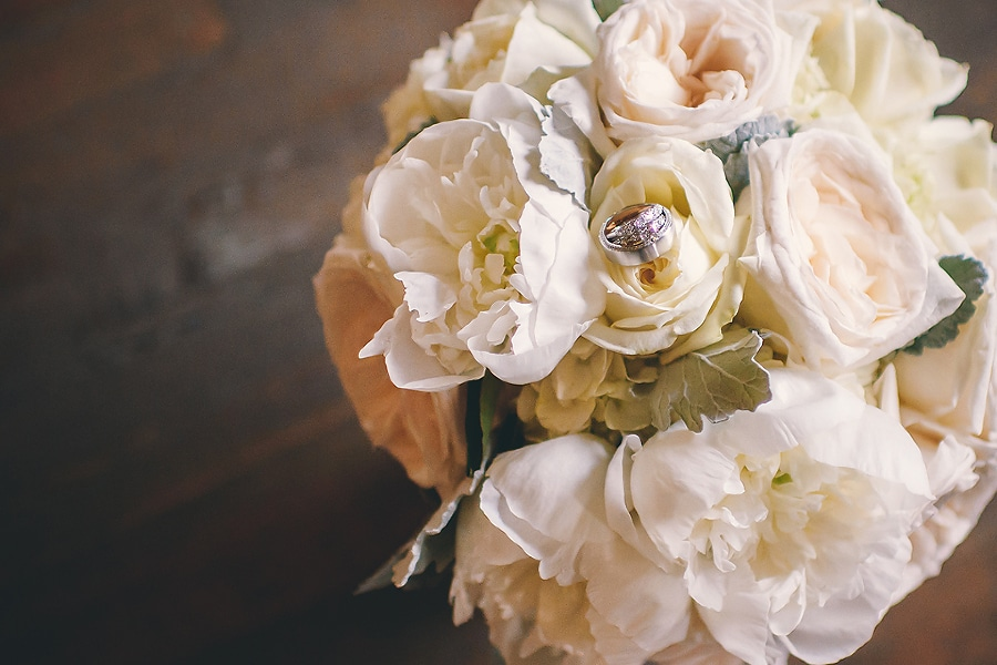 wedding rings from diamonds direct on a peony and garden rose bouquet