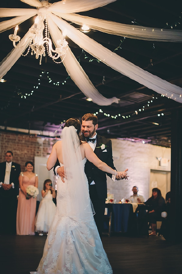 Bride and groom's first dance under the chandelier at the Bottle Factory venue