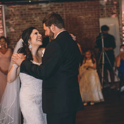 Bride smiling at her new husband during their first dance at the Bottle Factory