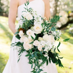 Lush cascading bouquet created by Floressence features white roses and deep greenery