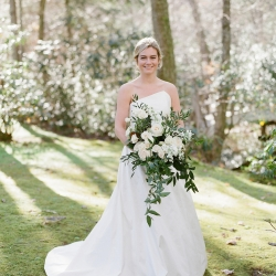 Bride poses for Krystal Kast Photography holding a lush cascading bouquet created by Floressence