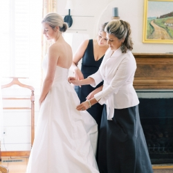 Brides mother helps button her dress captured by Krystal Kast Photography