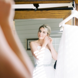 Bride puts on her jewelry as she prepares for her fall wedding in Highlands, North Carolina