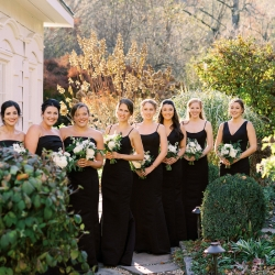 Bridesmaids pose for Krystal Kast Photography wearing elegant black gowns and holding stunning white bouquets created by Floressence