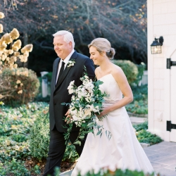 Bride walks with her father before her wedding ceremony panned by Magnificent Moments Weddings