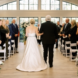 Bride is escorted down the aisle by her father during her fall wedding at Old Edwards Inn