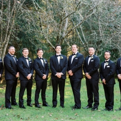 Groom smiles with his groomsmen who are wore black suites accent with white floral boutineers