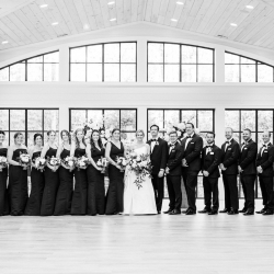 Bridal party poses in elegant black gowns and suits during a fall wedding captured by Krystal Kast Photography
