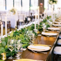 Long farmhouse tables lined with greenery garland and soft candle light are the perfect design touches created by Magnificent Moments Weddings