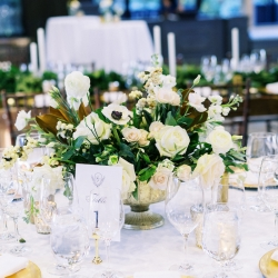 Low centerpieces created by Floressence feature gold vases and soft white florals